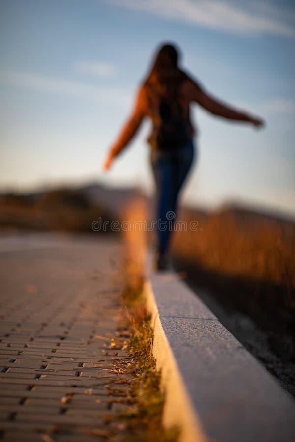 Mulher bonita que anda e que equilibra no freio ou no meio-fio da rua durante o por do sol imagem de stock