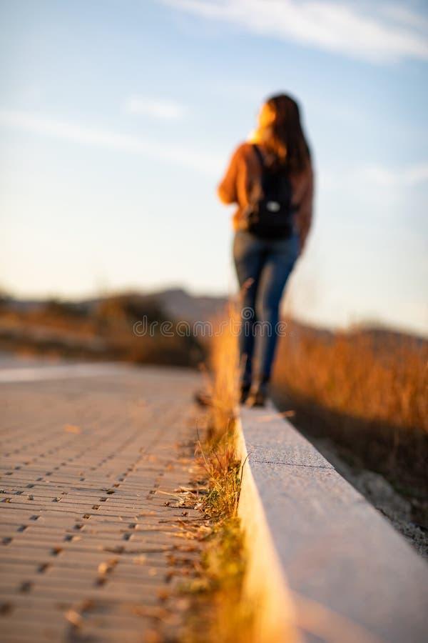 Mulher bonita que anda e que equilibra no freio ou no meio-fio da rua durante o por do sol fotos de stock