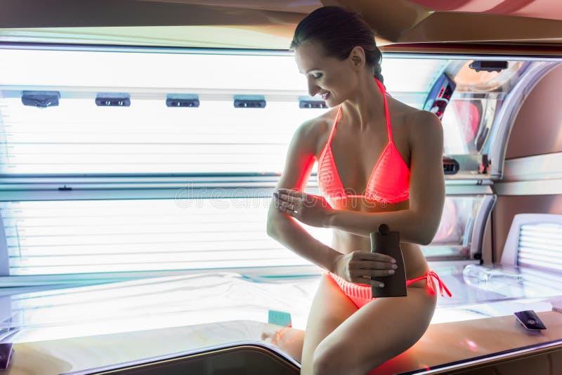 Mulher bonita que aplica o óleo nutritivo em sua pele antes de bronzear-se interno foto de stock royalty free