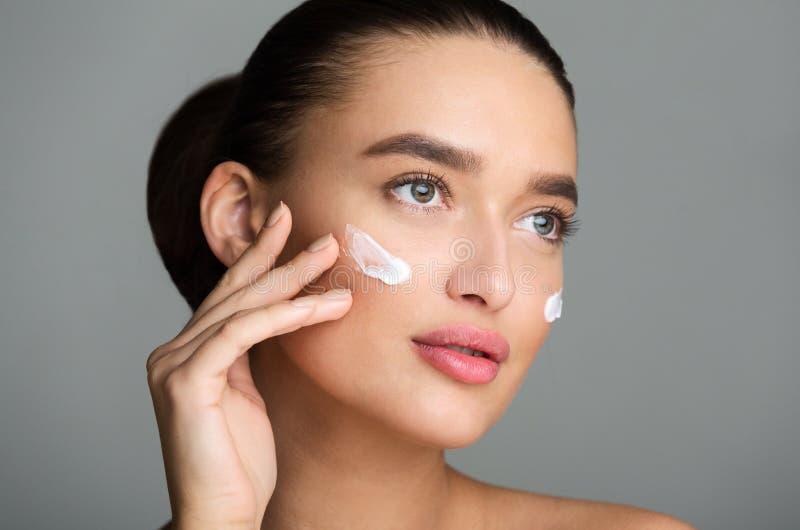 Mulher bonita que aplica o creme de cara e que olha afastado fotografia de stock royalty free