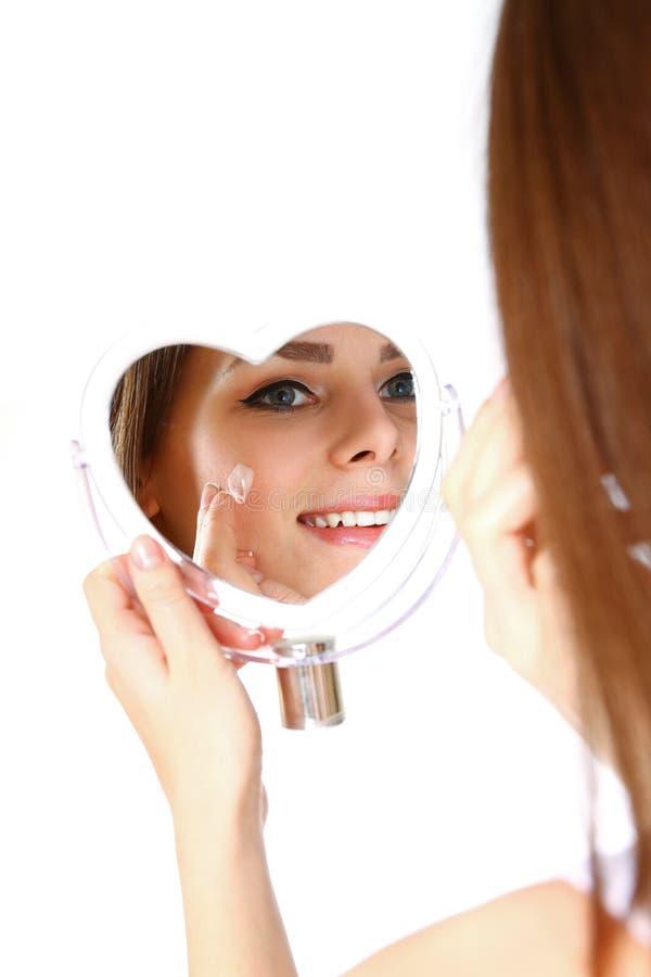 Mulher bonita que aplica o creme na cara no fundo branco fotografia de stock