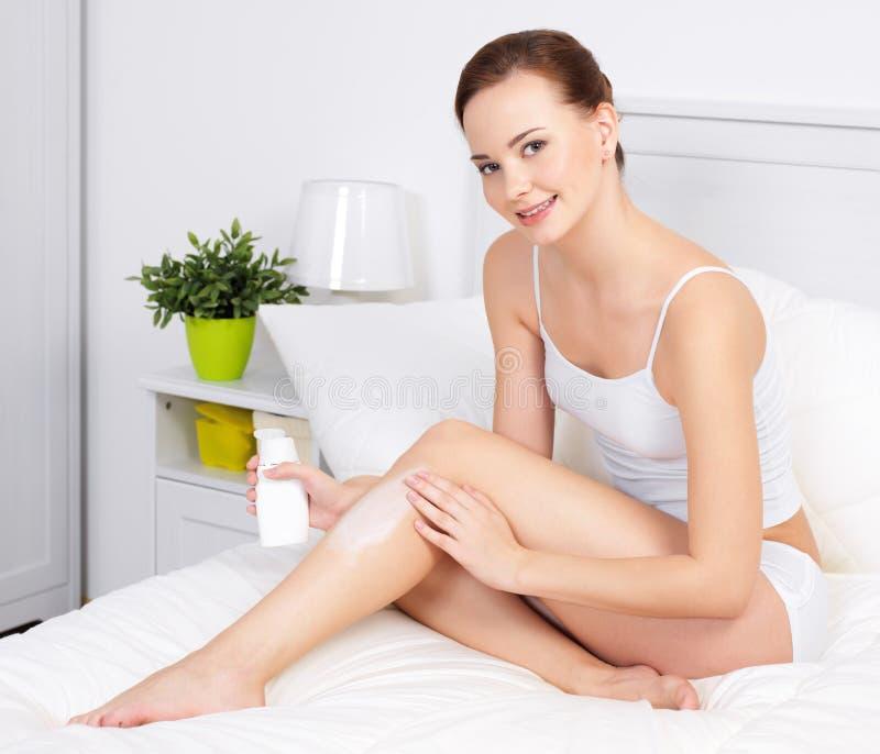 Mulher bonita que aplica o creme para a pele nos pés fotos de stock royalty free
