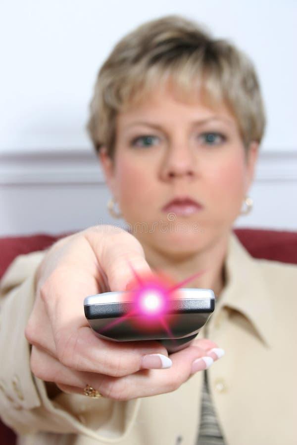 Mulher bonita que aponta o telecontrole com luz sobre foto de stock