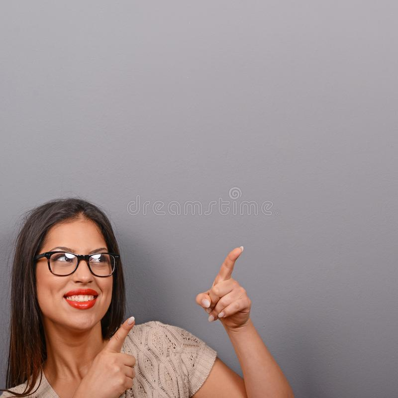 Mulher bonita que aponta para anular a área contra o fundo cinzento imagens de stock