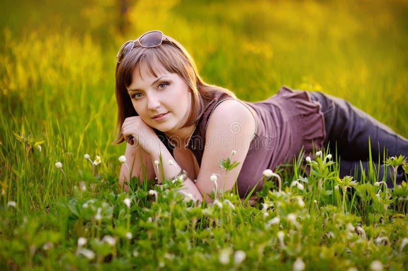 Mulher bonita que aprecia o campo da margarida imagem de stock