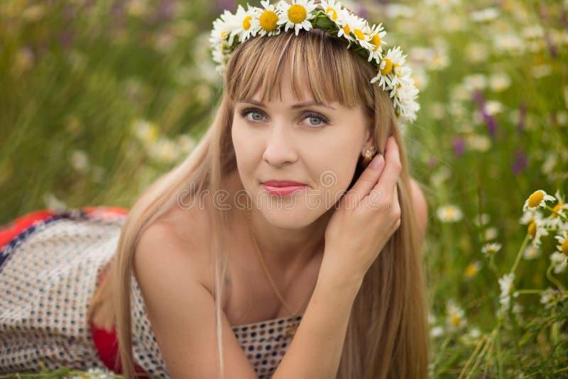 Mulher bonita que aprecia o campo da margarida, fêmea agradável que encontra-se para baixo no prado das flores, relaxamento bonit fotos de stock royalty free