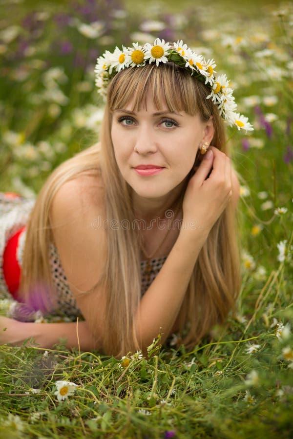 Mulher bonita que aprecia o campo da margarida, fêmea agradável que encontra-se para baixo no prado das flores, relaxamento bonit fotos de stock
