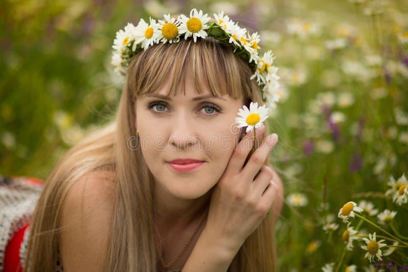 Mulher bonita que aprecia o campo da margarida, fêmea agradável que encontra-se para baixo no prado das flores, relaxamento bonit imagem de stock