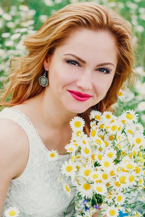 Mulher bonita que aprecia o campo da margarida na mola imagens de stock
