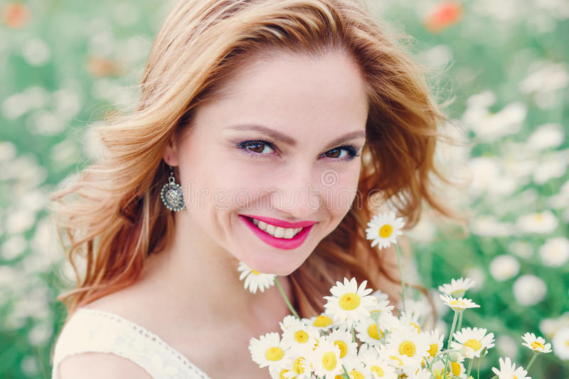 Mulher bonita que aprecia o campo da margarida na mola imagens de stock royalty free