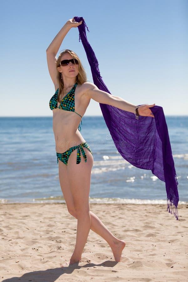 Mulher bonita que aprecia-se na praia a praia imagem de stock