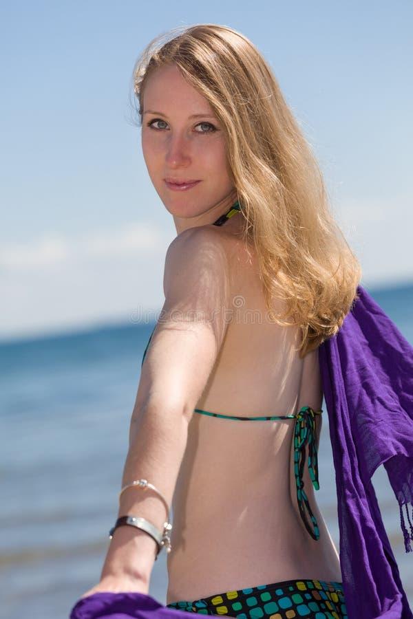 Mulher bonita que aprecia-se na praia a praia imagens de stock