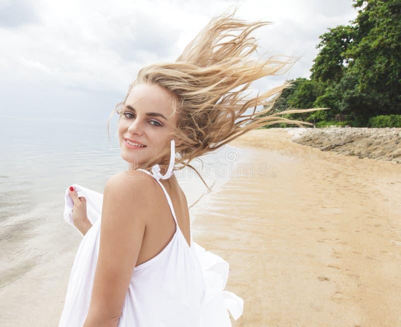 A mulher bonita que apreciam o verão na praia e o vento fundem seu h fotografia de stock