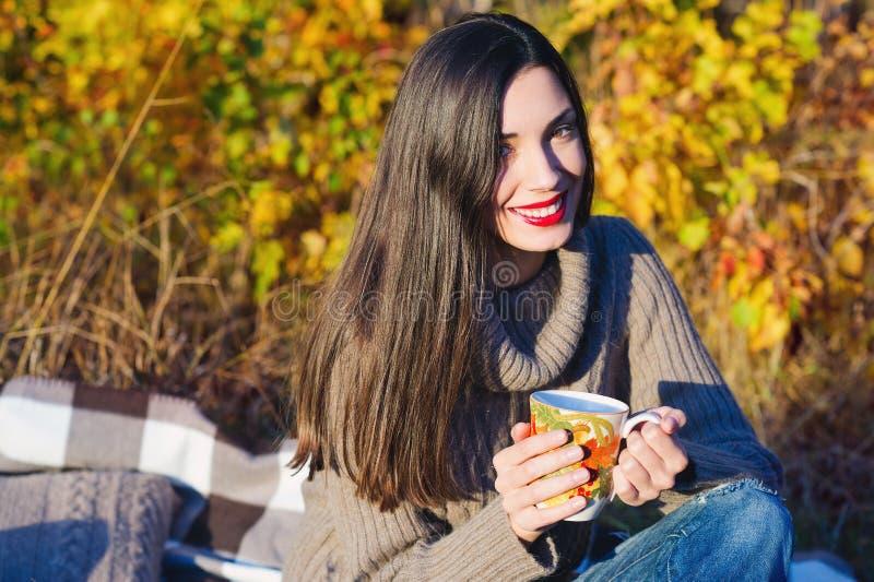 Mulher bonita que bebe o chá quente fora imagem de stock royalty free