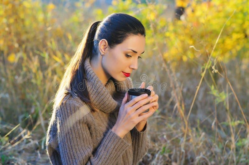 Mulher bonita que bebe o chá quente fora foto de stock royalty free