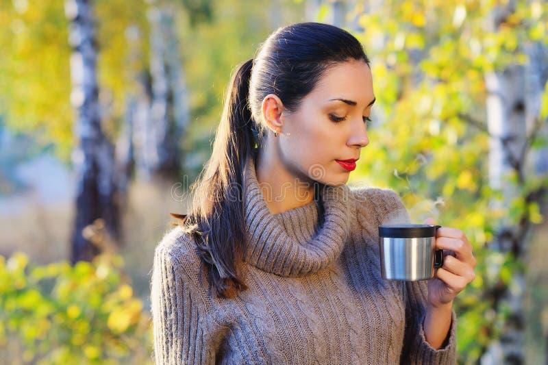 Mulher bonita que bebe o chá quente fora fotos de stock royalty free