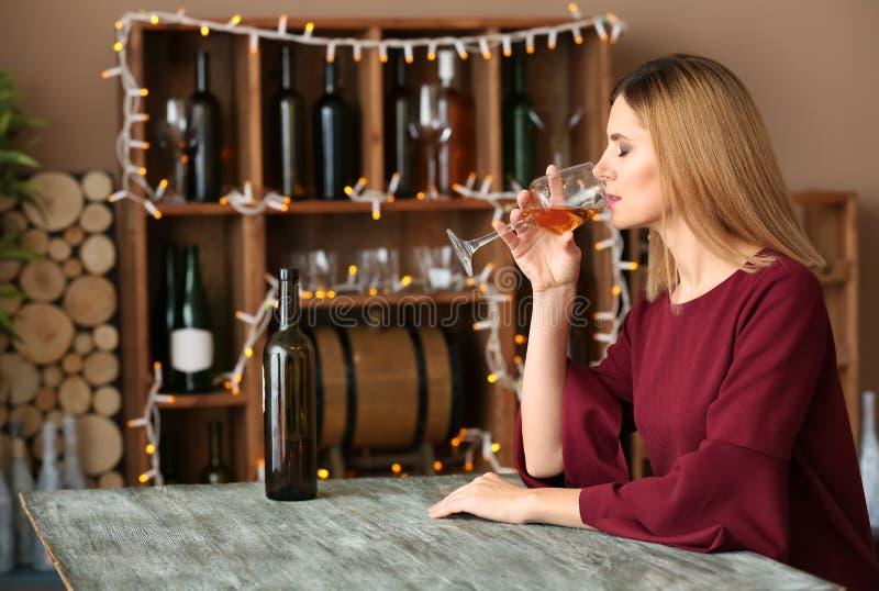 Mulher bonita que bebe o vinho saboroso na tabela na barra imagem de stock royalty free