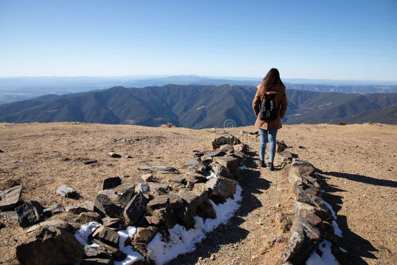 Mulher bonita que caminha no trajeto da montanha durante o inverno ou o outono em Catalonia ( Turo del Home - Espanha imagem de stock