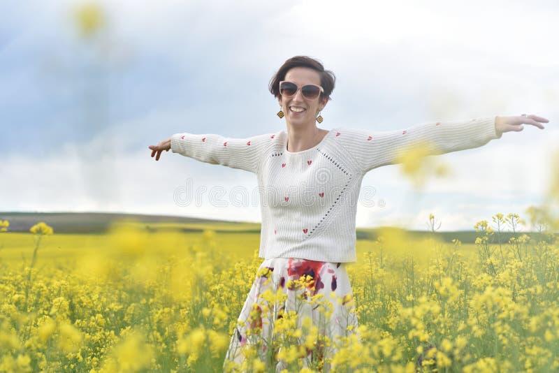 Mulher bonita que cheering no campo da colza e que aprecia o verão imagem de stock