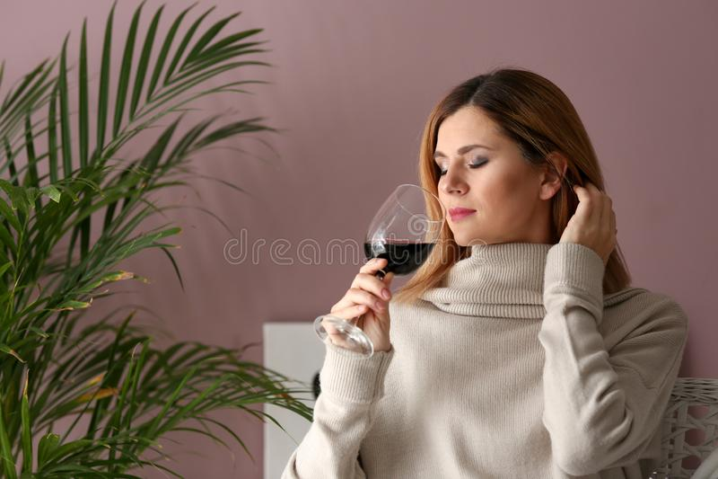 Mulher bonita que cheira o vinho saboroso em casa fotografia de stock royalty free