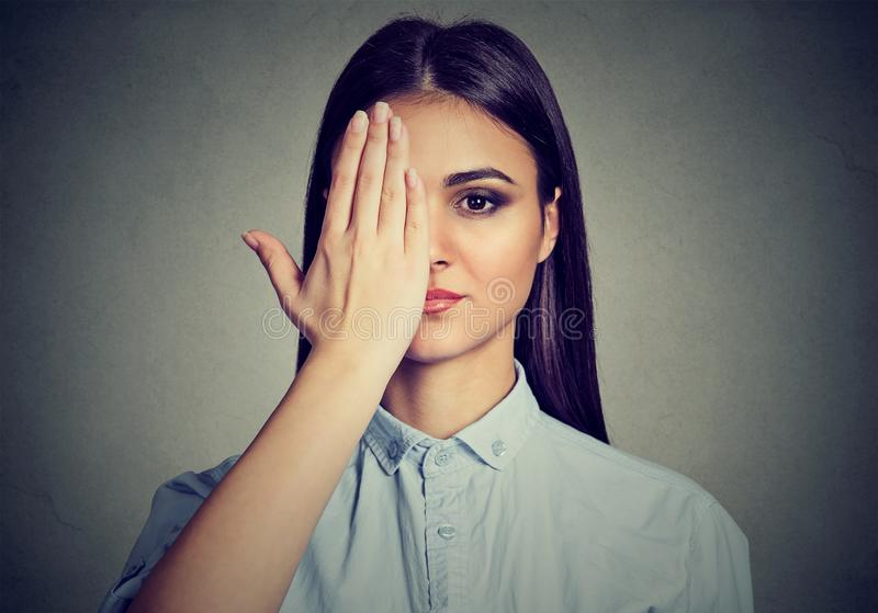 Mulher bonita que cobre um olho com a mão imagem de stock