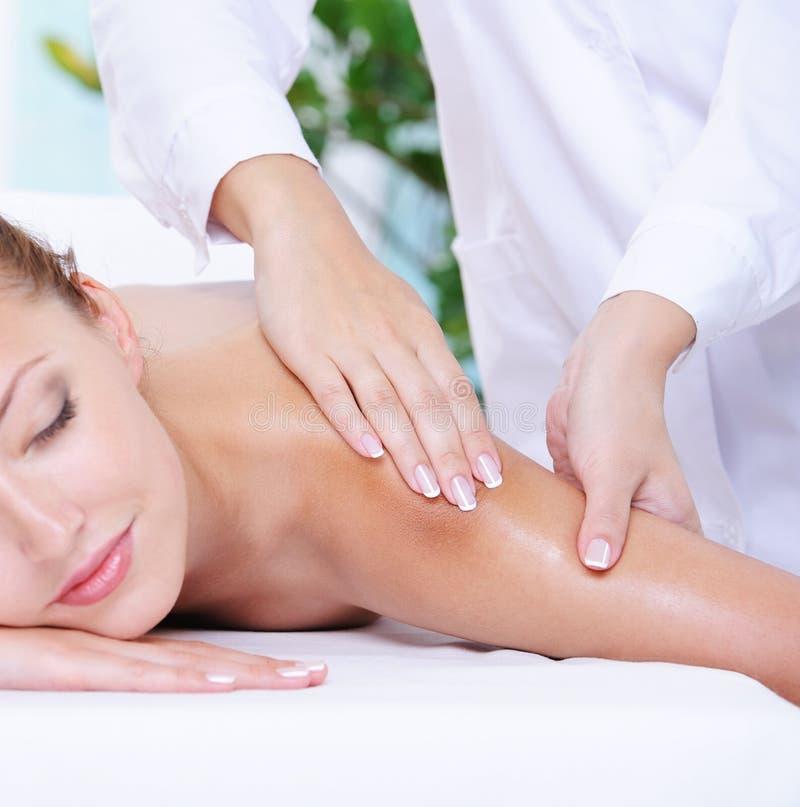 Mulher bonita que começ a massagem do ombro imagens de stock