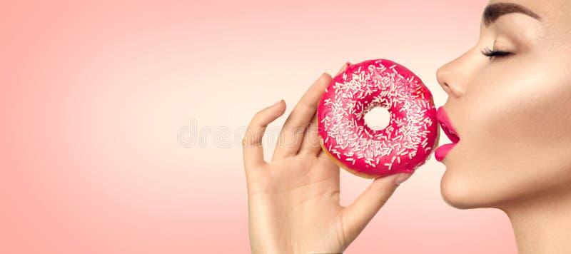 Mulher bonita que come a filhós cor-de-rosa imagem de stock
