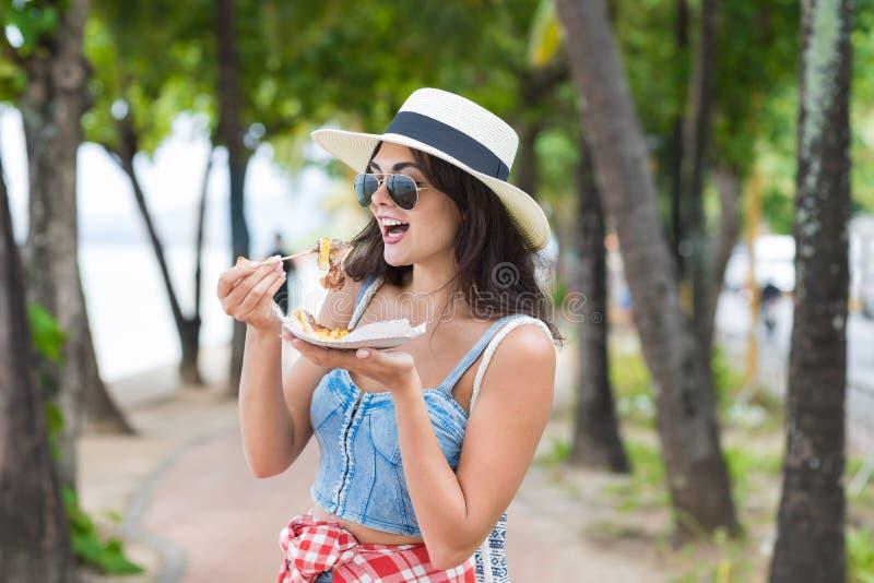 Mulher bonita que come o alimento asiático da rua que anda no parque na refeição exótica da tentativa do turista da moça do beira fotos de stock