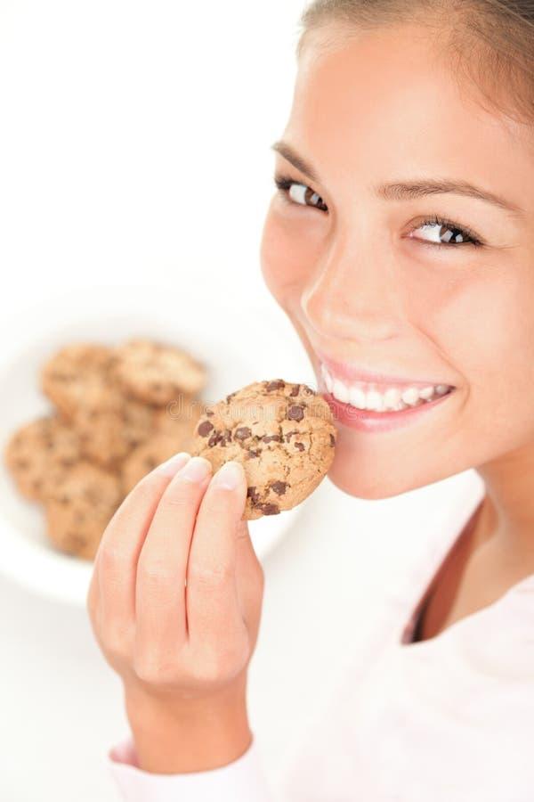 Mulher bonita que come o bolinho de microplaqueta de chocolate imagem de stock