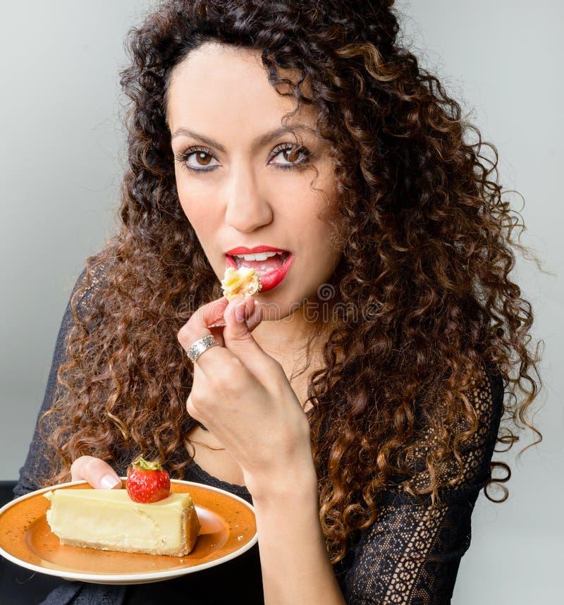 Mulher bonita que come o bolo de queijo imagens de stock
