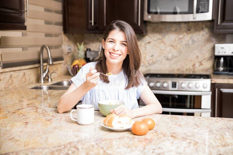 Mulher bonita que come o café da manhã em casa fotografia de stock