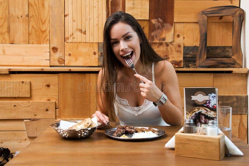 Mulher bonita que come o prato tradicional de Balcãs fotos de stock royalty free