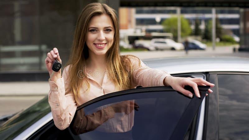 Mulher bonita que compra o veículo novo, guardando chaves e sorrindo na câmera, aluguer de carros imagem de stock royalty free
