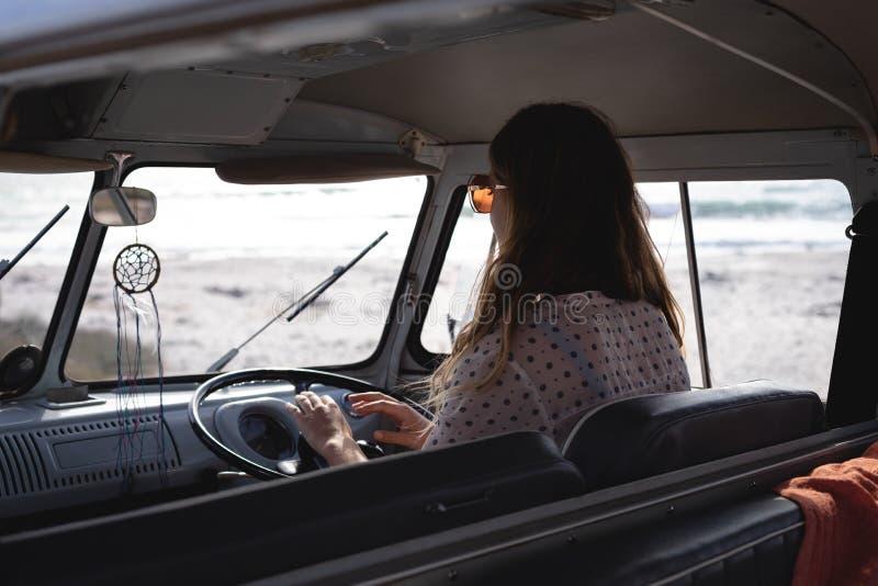 Mulher bonita que conduz uma camionete de campista na praia em um dia ensolarado imagens de stock royalty free