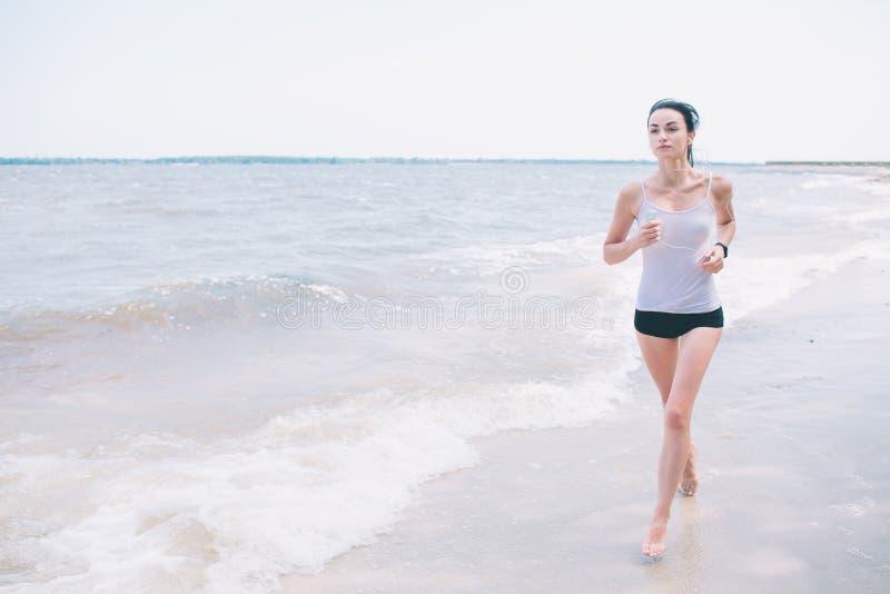 Mulher bonita que corre durante o por do sol Modelo novo da aptidão perto do beira-mar Vestido no sportswear foto de stock royalty free