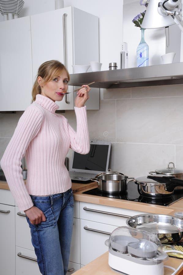 Mulher bonita que cozinha em uma cozinha moderna imagens de stock