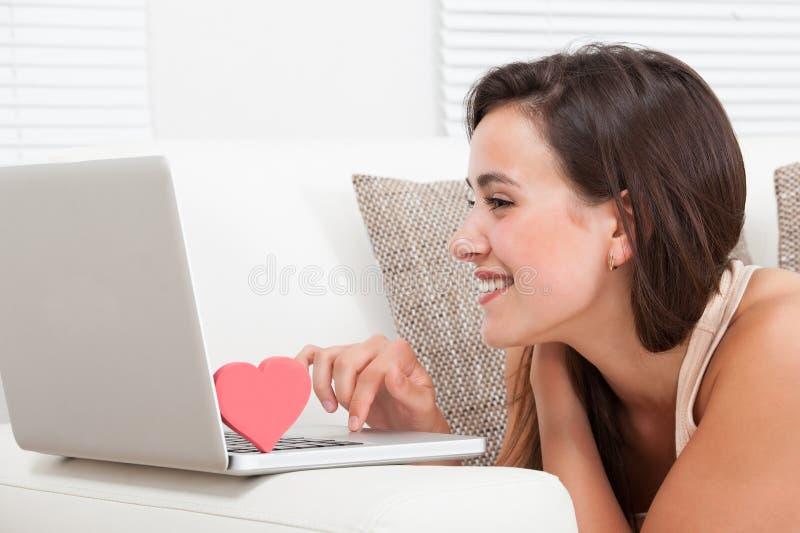 Mulher bonita que data em linha no portátil imagens de stock