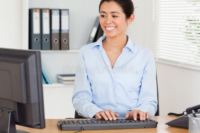 Mulher bonita que datilografa em um teclado ao sentar-se foto de stock