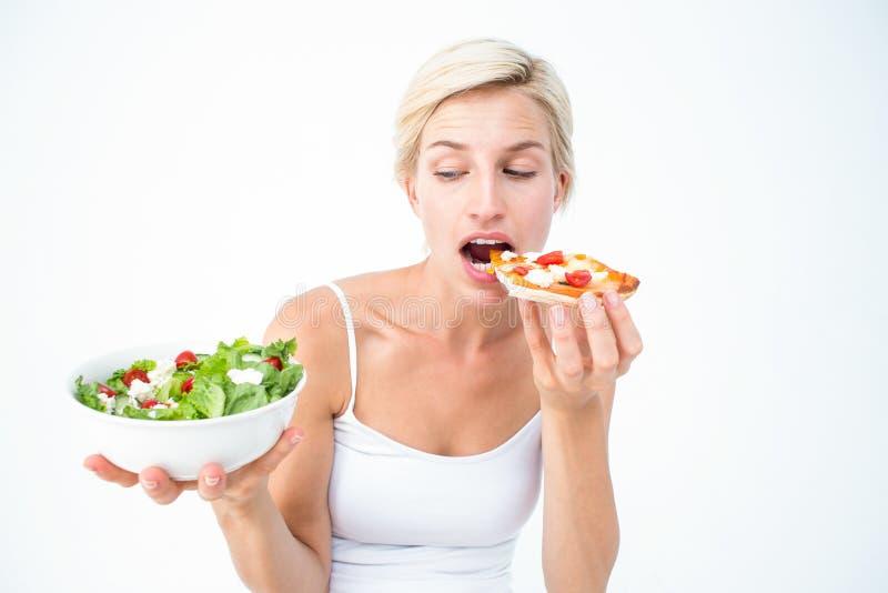 Mulher bonita que decide comendo a pizza um pouco a salada imagens de stock