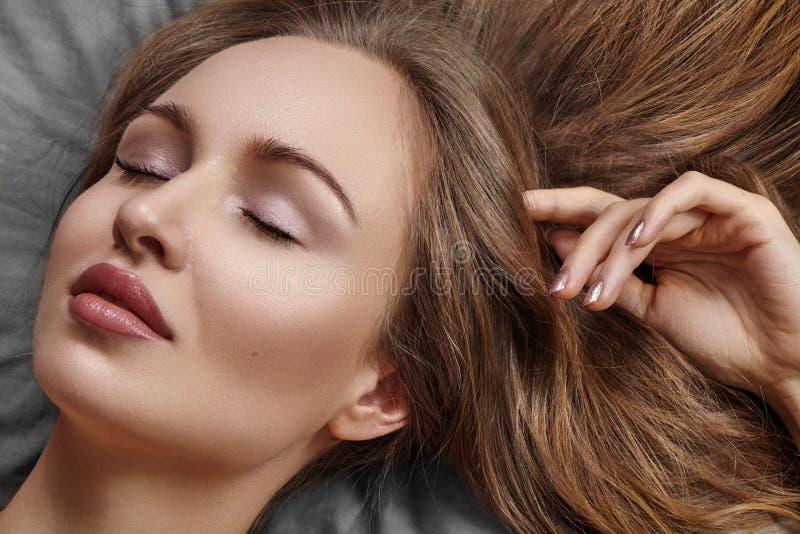 Mulher bonita que dorme ao encontrar-se na cama com conforto Sonhos doces Modelo 'sexy' com o cabelo encaracolado que relaxa em f fotos de stock