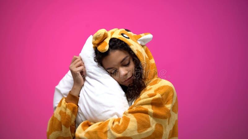 Mulher bonita que dorme nos pijamas do girafa, roupa confortável para o sono da noite imagem de stock