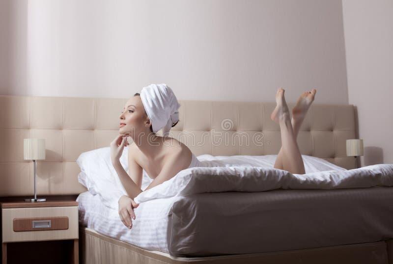 Mulher bonita que encontra-se na cama após ter tomado o chuveiro imagens de stock royalty free