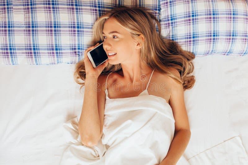 Mulher bonita que encontra-se na cama e que fala no telefone celular, positi imagem de stock royalty free