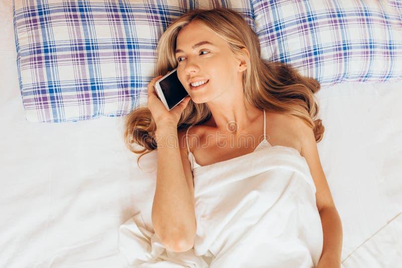 Mulher bonita que encontra-se na cama e que fala no telefone celular, positi foto de stock
