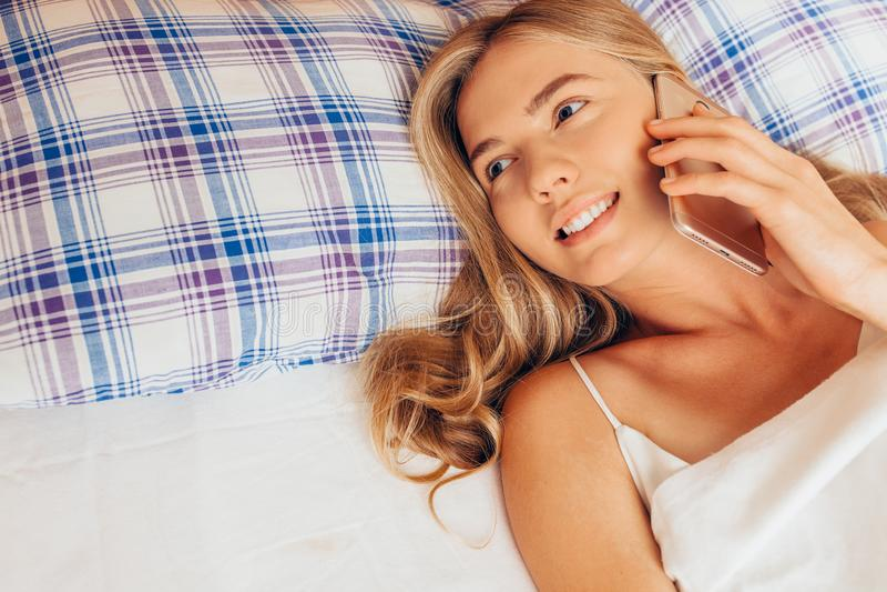 Mulher bonita que encontra-se na cama e que fala no telefone celular, positi fotografia de stock