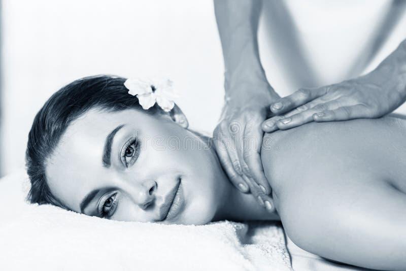 Mulher bonita que encontra-se na tabela da massagem e que aprecia a massagem foto de stock
