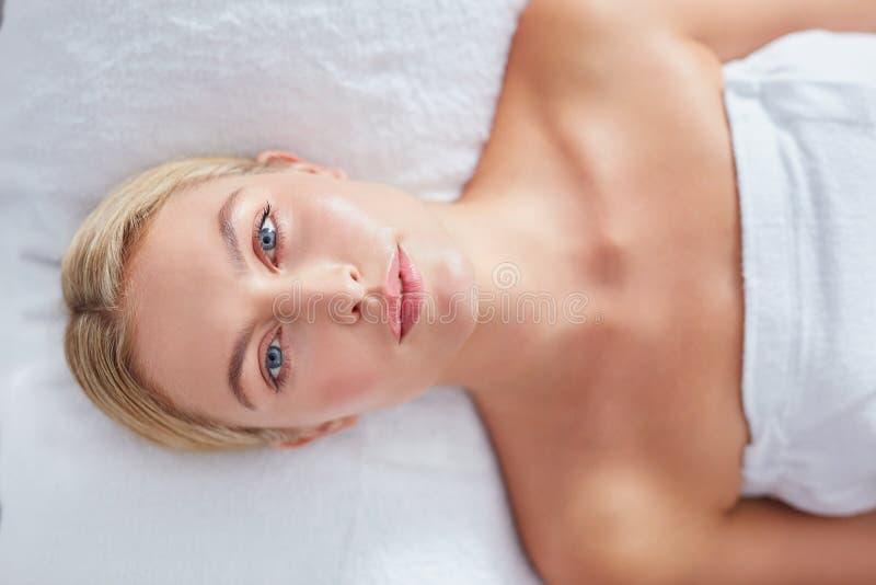 Mulher bonita que encontra-se na tabela da massagem no dayspa foto de stock royalty free