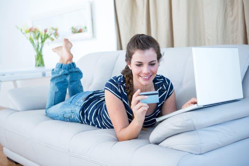 Mulher bonita que encontra-se no sofá que faz a compra em linha imagens de stock royalty free