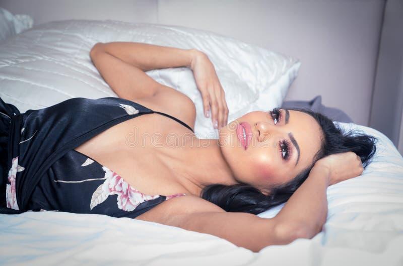 Mulher bonita que encontra-se no vestido vestindo da cama fotografia de stock royalty free