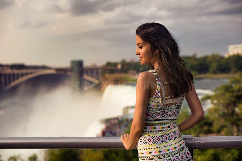 Mulher bonita que enjoing a ideia da queda de Niagara foto de stock royalty free